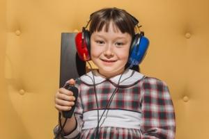 Badanie słuchu u dziewczynki w kabinie audiometrycznej.