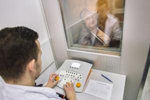 Badanie słuchu w kabinie ciszy z operatorem audiometru.
